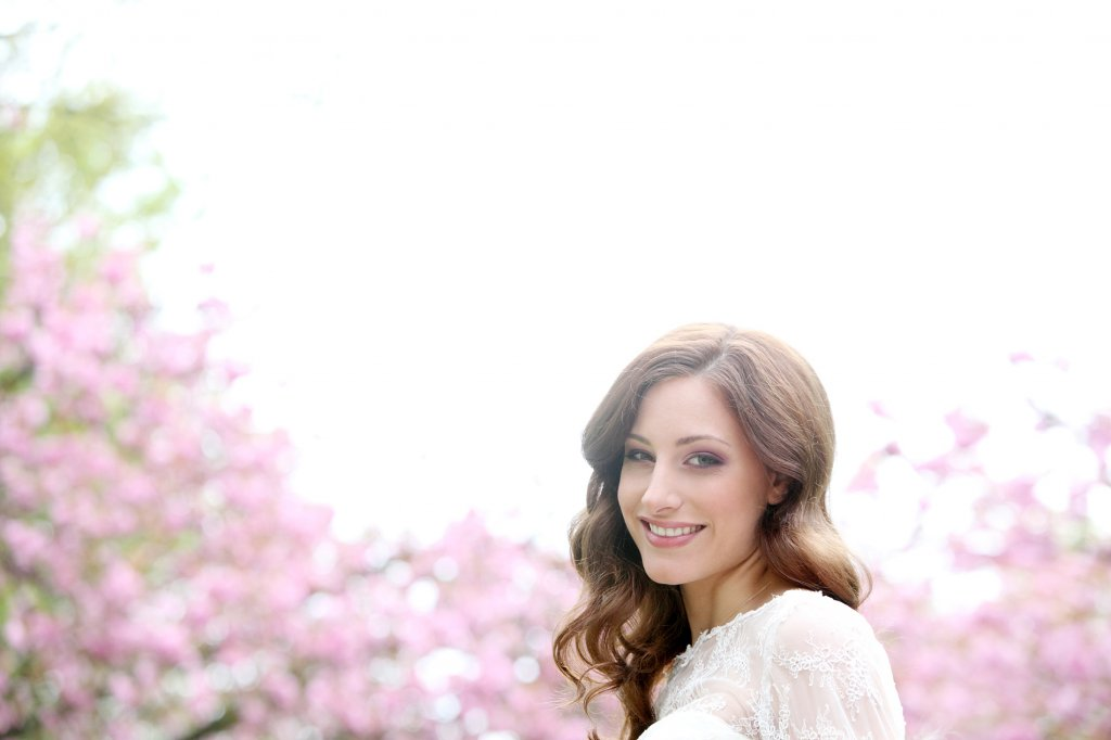 Photo styled bride smiles with cherry blossoms as a backdrop