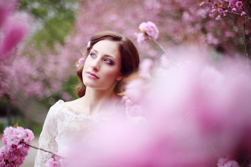 Photo bride looks up in the cherry blossom tree