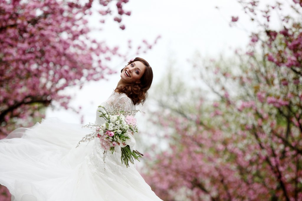 Photo bride dancing in the midst of cherry blossom trees, holding her bouquet