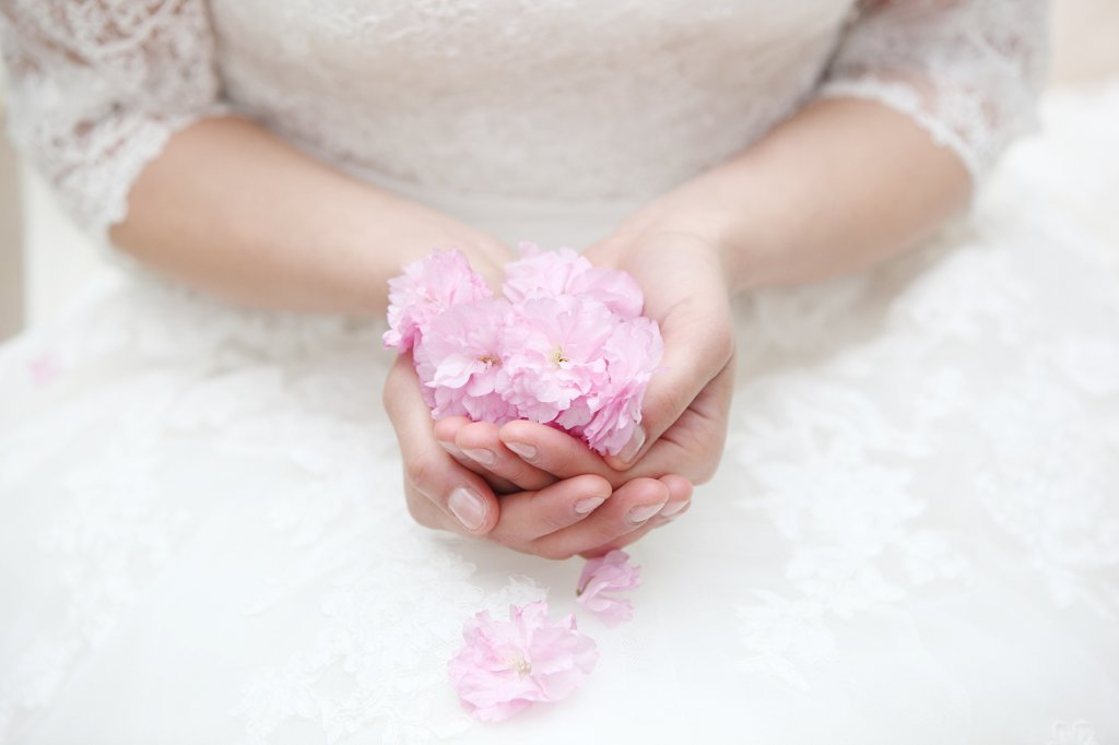 Photo blurry image of bride holding cherry blossom petals in her hands