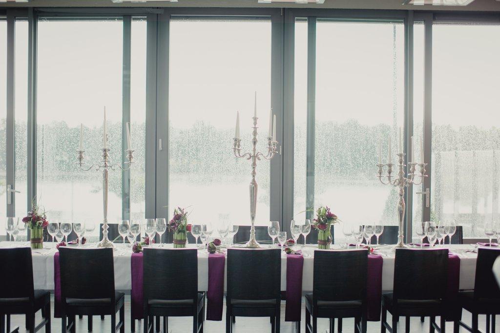 Photo Festtafel mit dunklen Stühlen und hohen silbernen Kerzenleuchtern.