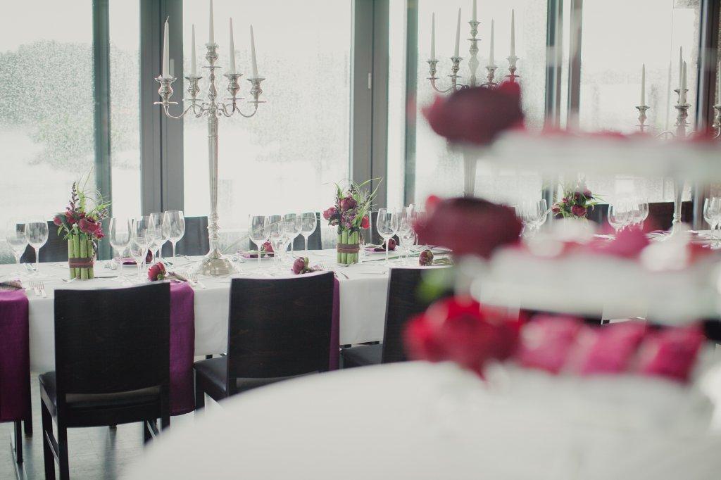 Photo Festsaal mit vom Tisch fallenden Servietten, beerenfarbig.