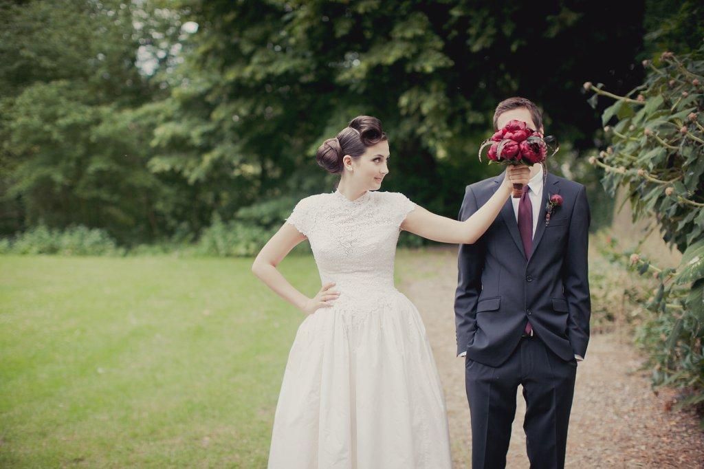 Photo Braut hält Bräutigam ihren Brautstrauss vors Gesicht.