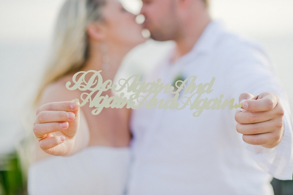 Photo Bride and groom kissing, holding up a singn reading