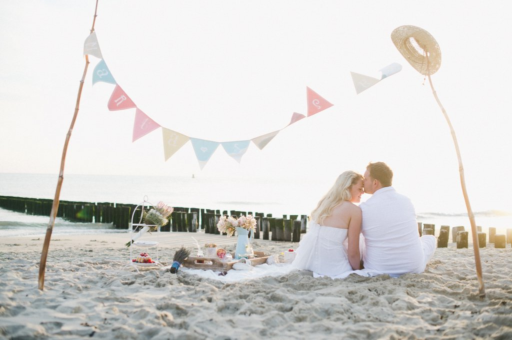 Photo romantic scene at the beach picnic, bride and groom look into the sunset