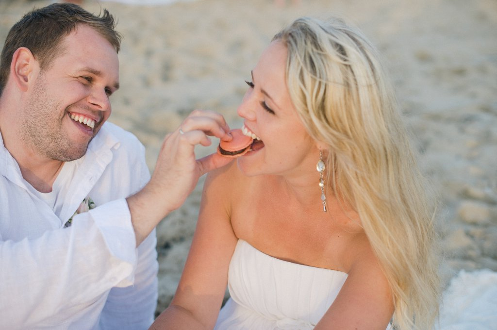 Photo groom feeds bride at the beach picnic