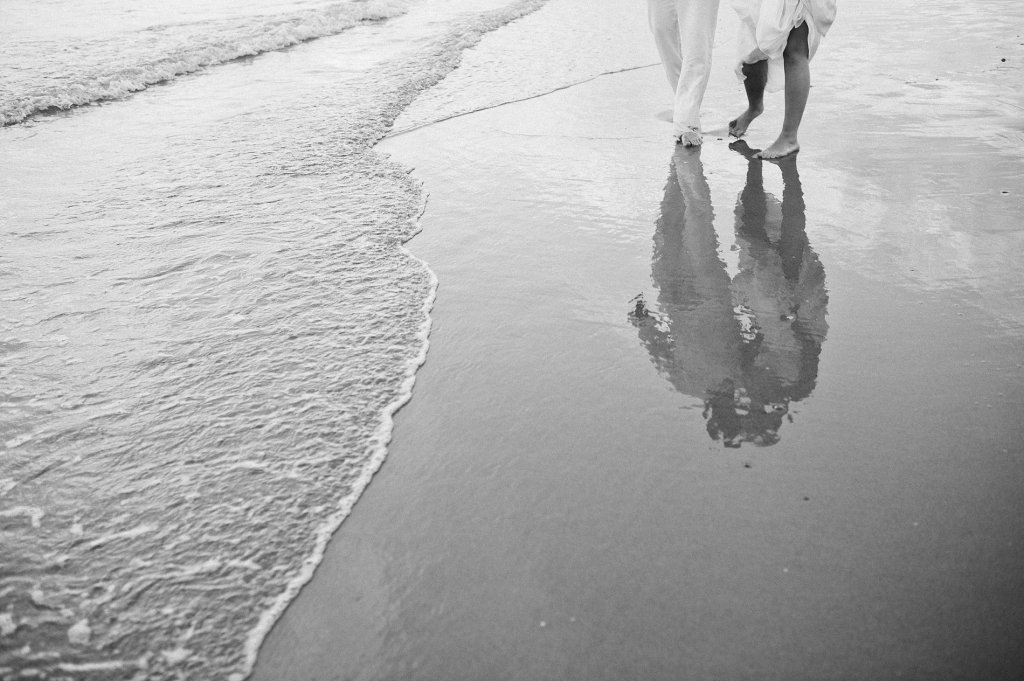 Photo reflection of bride and groom in the wet sand