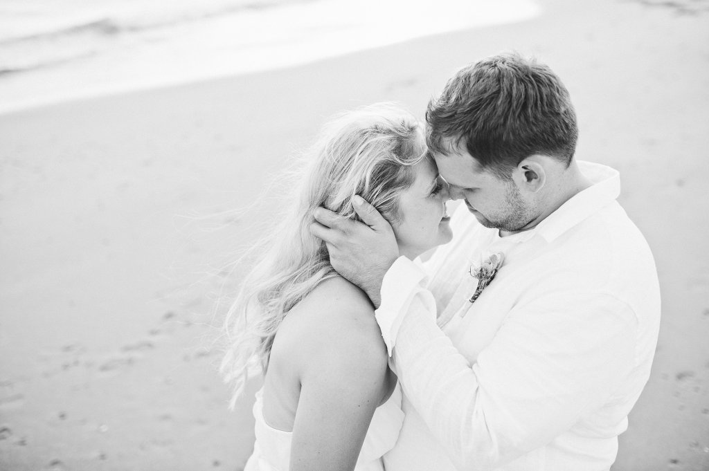 Photo groom holds brides hair gently back, as he attempts to kiss her