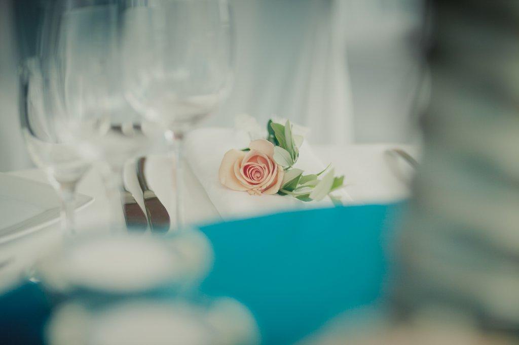 Photo Tischdekoration mit Rose auf weisser Stoffserviette.