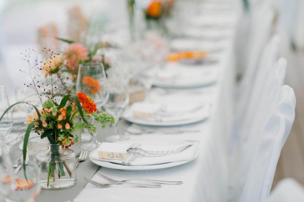 Photo Tischdekor mit Wiesenblumen in Orange- und Pudertönen.